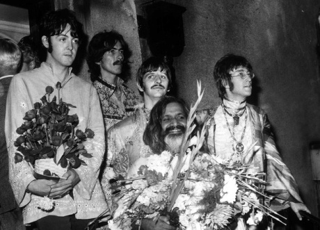The Beatles with the Maharishi Mahesh Yogi who is clutching bundles of flowers Beatles left to right are: Paul McCartney, George Harrison, Ringo Starr and John Lennon. August 1967.
